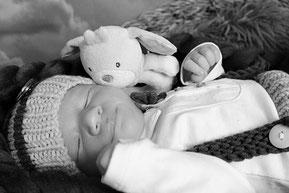 Neugeborener Junge mit Kuscheltier