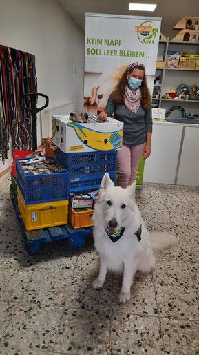 Frau mit weißem Schäferhund und großer Futterspende