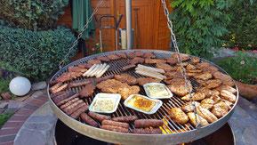 Ein Schwenkgrill mit Grillkäse, Nackensteaks, Putenfleisch, Bratwurst, Minutensteaks und Kucchis.
