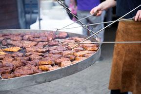 Ein Schwenkgrill mit Nackensteaks und Putenfleisch auf Buchenholz gegrillt.