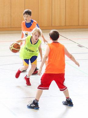 Drei Jugendliche beim Basketballspiel in einer Turnhalle.