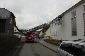 Mit Hilfe einer Drehleiter befestigt die Feuerwehr Schwalbennisthilfen in größerer Höhe am Haus unter einem Dachüberstand.