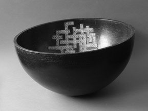 a smoked and polished bowl form bearing a crossword puzzle motif