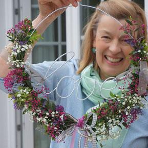 Blumenkranz mit Sommerblumen binden auf einem Kleiderbügel