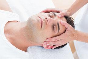 Une séance d'Access Bars. Un homme allongé sur le dos, détendu, les yeux fermés. Le praticien touche un des 32 points énergétiques de la tête afin d'éliminer les mémoires inutiles.