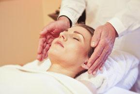 Une séance de Reiki. Une femme allongée sur le dos, détendue, les yeux fermés. Les mains du praticien entoure ses temps sans contact physique