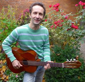 Alexei Beliakov hält seine Gitarre zum Spielen bereit und steht vor einem  blühenden Rosenbusch.