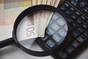 Taschenrechner mit Lupe und mehreren aufgefächerten 50-Euro-Banknoten - alles übereinander liegend