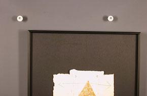 Bildaufhänger Metall auf schwarzem Alurahmen montiert. Hängung mit Exzenter auf Gibswand.