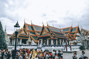 people standing in front of the Grand Palace in Bangkok on a cloudy day.