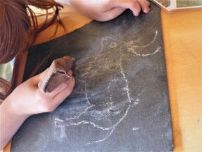 Kind ritzt Abbildung eines Rindes in Schieferplatte