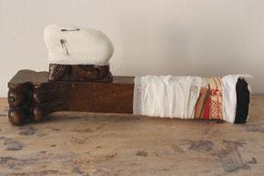"""Eva Hradil, """"Vorderbein links"""" oder """"amputiert"""", 2017, geschnitztes Nussholz aus Historismus, Verbandsmull, Teile von Kleidungsstücken aus Buenos Aires, Sicherheitsnadeln, ca. 16 x 37 x 9 cm"""
