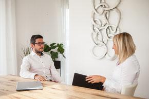 Kerstin in der Funktion als Coach sitzt mit Klient an Tisch und bespricht Situationen aus dem Management.