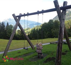 Mädchen auf Schaukel vor Alpenpanorama