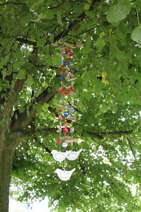 Windspiel aus Kronkorken im Baum