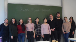 "A Group picture of the team that built the website. 10 people are standing, smiling, in front of a blackbord which reads ""Queer Migrants Welcome"""