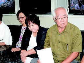 記者会見で訴訟への参加を那覇地裁に申し立てたと発表する平安座会長(右端)=5日、県庁