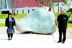病院名を刻んだ石碑に揮毫し、除幕式後に記念撮影に応じる伊江さん(右)。左は篠﨑院長=16日午後、八重山病院前