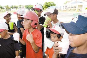 練習の合間に水分補給で喉を潤した少年アカハチのメンバー=7月31日午前、大浜小学校グラウンド