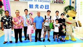 2018人目の到着客として記念品を贈られた田畑尚吾さん一家とミス八重山ら=1日午後、新石垣空港
