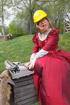 Corinna in rotem Ballkleid mit gelbem Baustellenhelm und Schreibmaschine auf einem Holzpferd sitzend