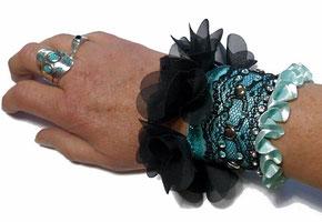 photo d'un bracelet manchette original de créateur noir et bleu turquoise à volant de pétales en tulle et froufrous porté sur le poignet