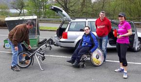 Drei Menschen ohne Rollstuhl und ein Mensch im Rollstuhl
