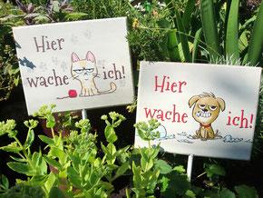 """""""Hier wache ich"""" Hunde- und Katzenschild nebeneinander in ein Blumenbeet gesteckt."""