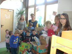 Kindergartenkinder überreichen zusammen mit Erzieherinnen die Geschenke für's Kinderdorf an Jana und Janina vom Rat