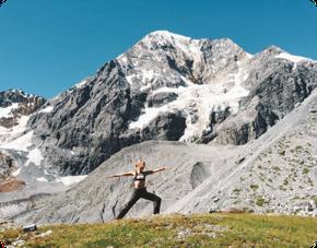 Frau macht in den Bergen Yoga