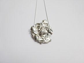 Un pendentif massif au design froissé est suspendu à une chaîne en argent.