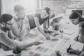 Zu sehen sind Menschen, die gemeinsam Ideen entwickeln, um ihr Unternehmen voranzutreiben
