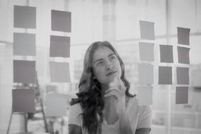 Zu sehen ist eine Frau, die intensiv reflektiert und Ihre eigenen Ideen auswertet
