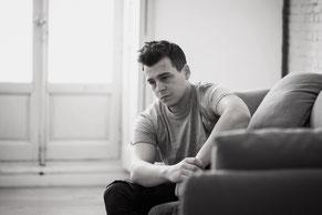 Zu sehen ist ein junger Mann, der mit leerem Blick traurig auf den Boden starrt