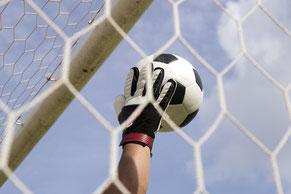 Das Bild zeigt die Hand eines Torwärters, der einen Fussball vor dem Netz fängt: Fokussierung stärken und mentale Blocken überwinden als häufiges Ziel im mentalen Coaching.