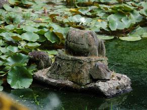 「ぶじかえる」の文字が刻まれた木彫りのカエルも