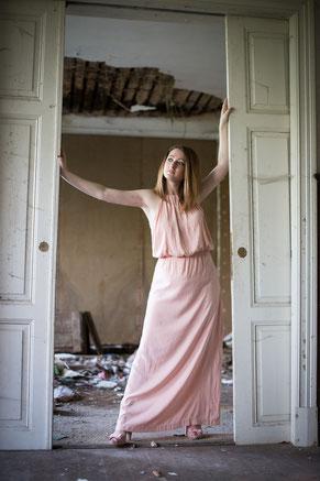 Frau in rose farbenen Kleid in einer zerfallenden Villa