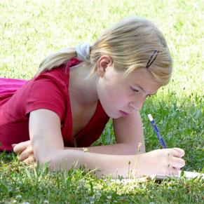 Ein Mädchen liegt in der Wiese und schreibt.