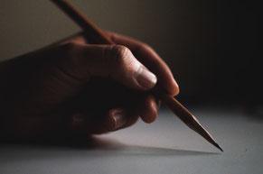 Auf dem Bild ist eine Hand zu sehen, die einen Bleistift hält. Für mehr Informationen, bitte den Bilduntertitel lesen.