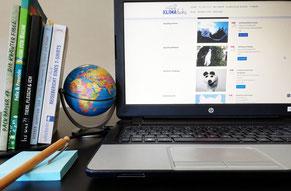 Laptop von vorne, zeigt KLIMAfuchs-Downloadmaterial. Daneben Globus und Bücher