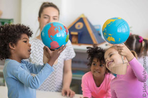 Erzieherin schaut mit Kindern auf kleinen Globus