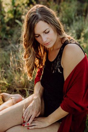 junge Frau in roter Strickjacke schaut über die Schulter