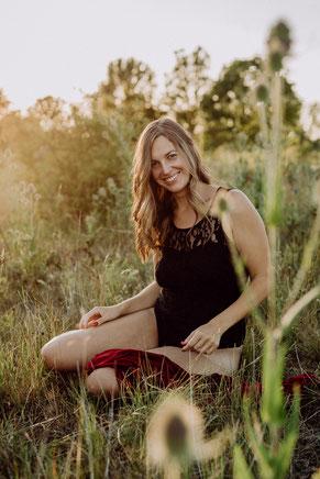 blonde Frau mit schwarzer Wäsche sitzt im Feld und lächelt