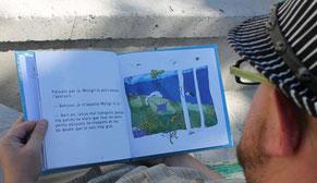 Un lecteur au chapeau lit sur un banc à Paris le livre Faribole et Mistigri