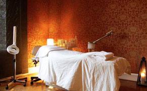 Massagebänk i rum med röd tapet
