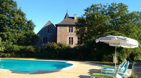 Château de Chanzé pool, sun umbrella and loungers on  a late spring day