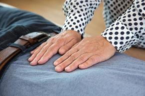 Zwei Hände auf dem Bauch während einer Behandlung