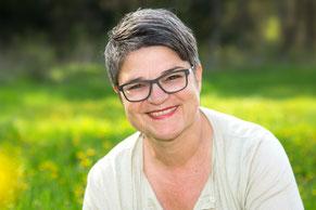 Portrait von Andrea Roth Hurni mit einer Wiese im Hintergrund