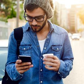 junger Mann mit Smartphone unterwegs draußen