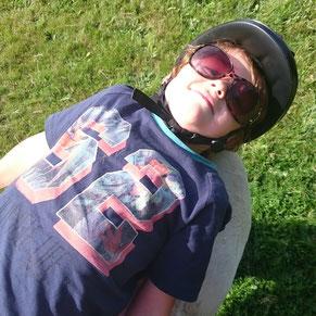 Jongetje ligt languit en ontspannen op het paard tijdens paardrijles